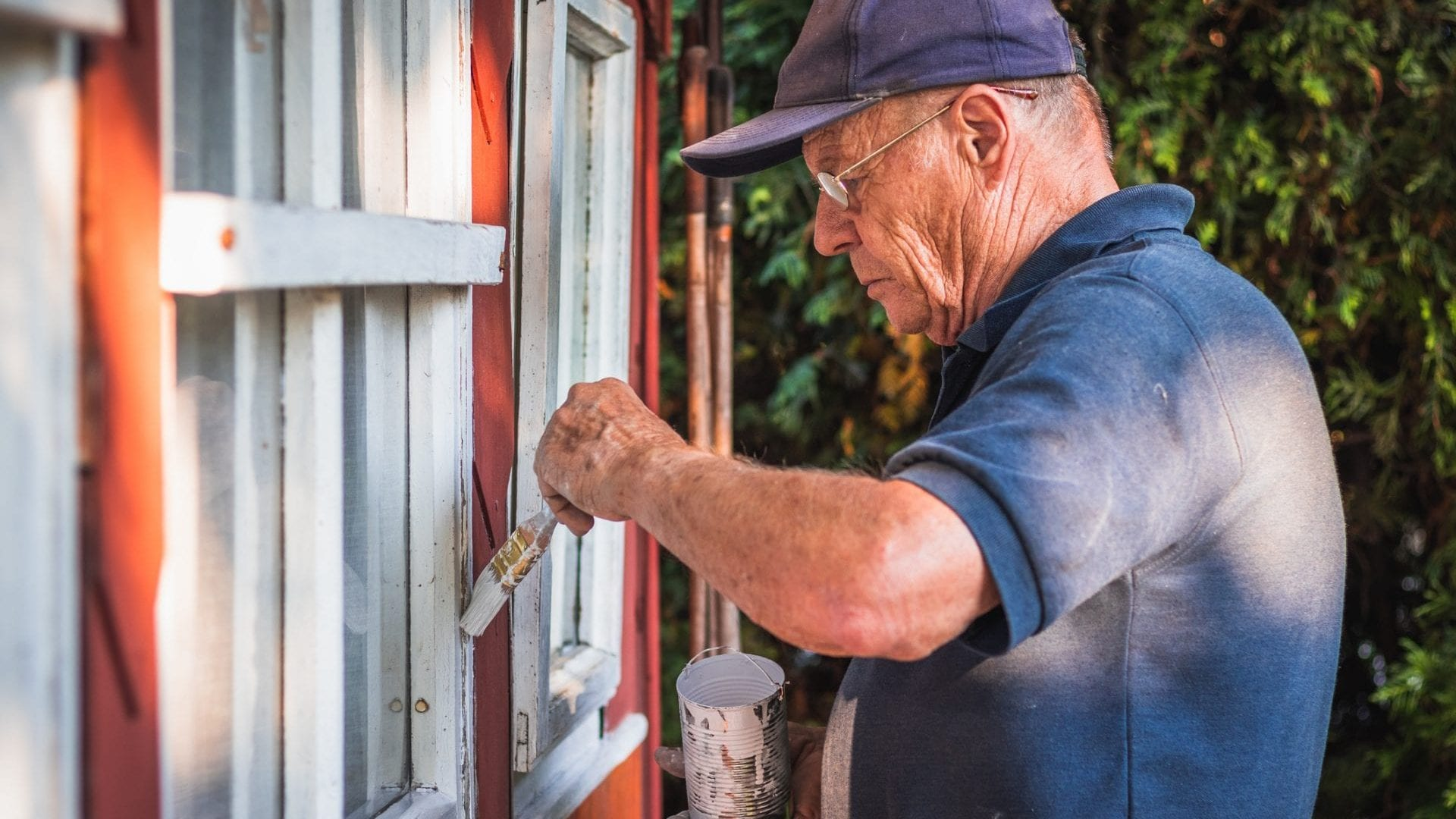 Active senior man painting window frame of wooden cabin. House improvemnet.